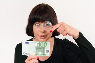 Eine Frau prüft Geldschein mit Lupe