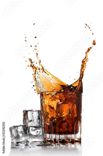 splash of cola in glass with ice cubes isolated on white