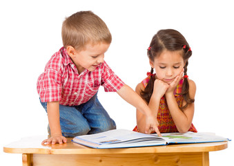 Two smiling children reading book on the desk