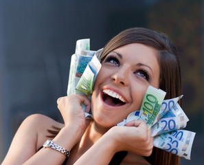 Beautiful ecstatic young woman with Euro bills