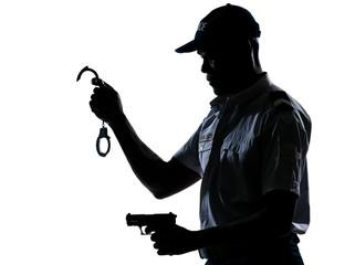 Policeman holding handcuffs and handgun