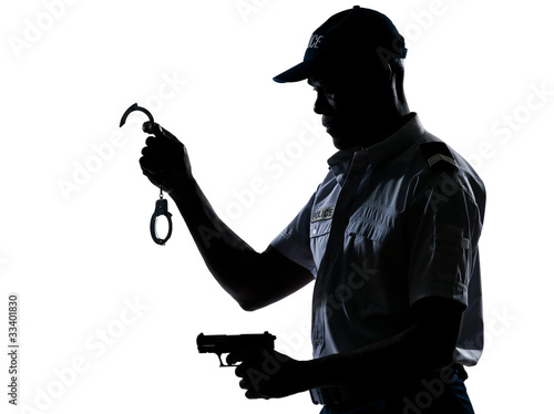 Policeman holding handcuffs and handgun