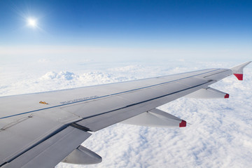 Airplane wing above the clouds and sun