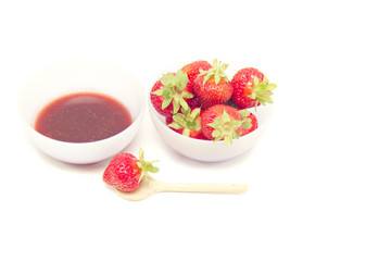 Glass pot with strawberry jam isolated on white