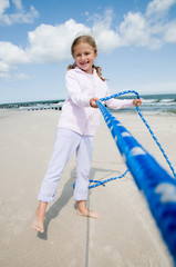 Tug-of-war - girl playing on the beach