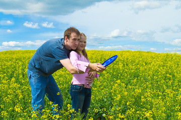 The father learns a daughter to launch frisbee on a meadow