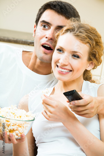 Young couple eating popcorn and watching TV together.