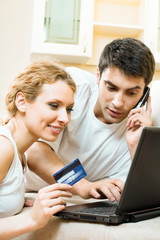 Smiling couple with laptop, paying by credit card in net store