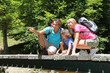 Family sitting on bridge over mountain river