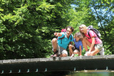 Family sitting on bridge over mountain river