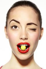 mujer guiñando un ojo mordiendo un caramelo