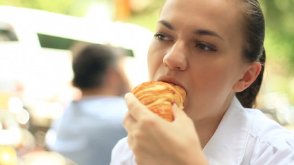 Attractive woman eating croissant in restaurant, steadicam