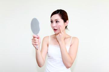 鏡を見て驚いた表情の女性