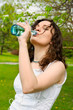 Young woman drinking water at outdoors