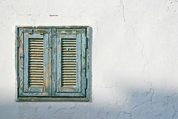 The old window with blue shutters on a white wall