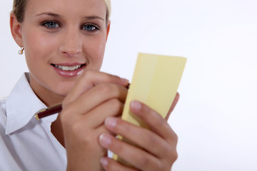 woman noting down something on a piece of paper