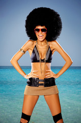 Woman with huge afro haircut close to water