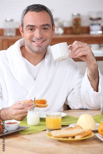 Man having breakfast in dressing gown