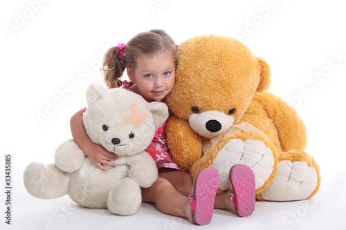 Little girl hugging two big teddy bears