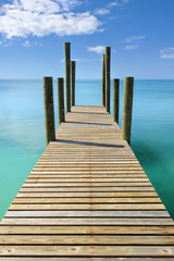 Wooden jetty leading in turquoise blue sea in Governor's Harbour