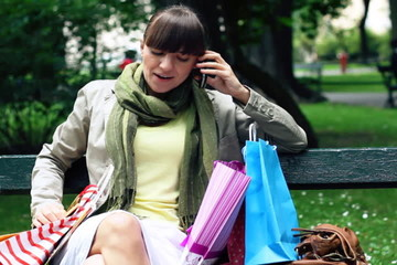 Woman sitting on bench after shopping and talking on the phone