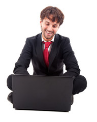 Smiling businessman sitting on the floor using his laptop