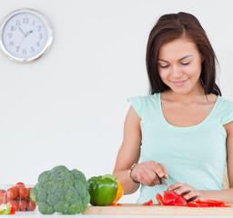 Smiling brunette slicing a pepper