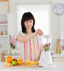 Attractive brunette woman putting vegetables in a mixer while st