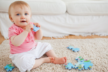 Cute blond baby playing with puzzle pieces while sitting on a ca