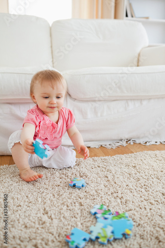 Lovely blond baby playing with puzzle pieces while sitting on a
