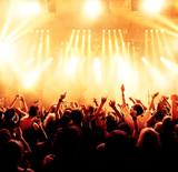 Koncert tłumu przed jasnożółtymi reflektorami scenicznymi