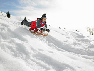 Pre-teen Boy On A Sled In The Snow