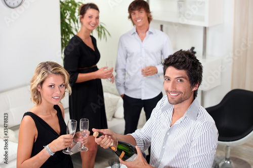 two well dressed couples drinking sparkling wine