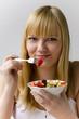 Junge Frau isst Obstsalat