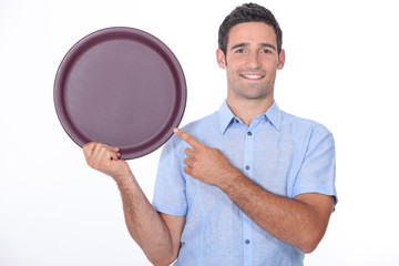 Smiling man pointing at an empty drinks tray