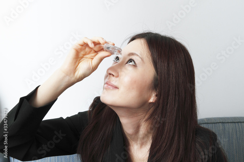 Business woman applying eye drops