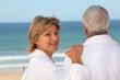 Older couple in bathrobes watching the ocean
