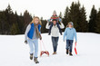 Young Family Walking Through Snow With Sled