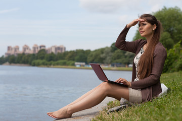 Young woman with laptop in the park.