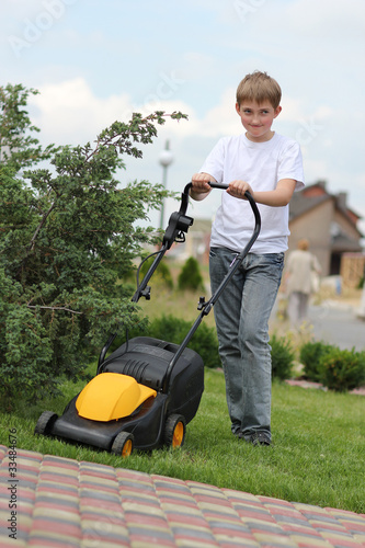 Teen boy mows the lawn mower electric