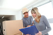 Woman with delivery man checking order contract