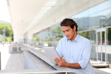 Man websurfing on electronic tablet outside