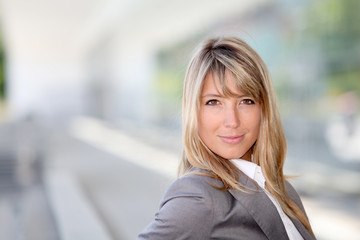 Portrait of businesswoman standing outside offices