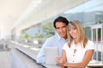 Couple websurfing on electronic tablet outside