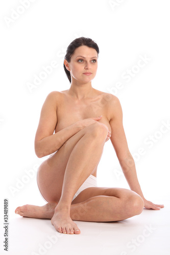 Semi naked young woman sitting hand over breasts