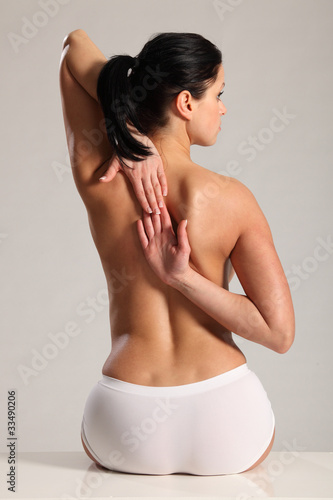 Back pain and stretch for semi nude young woman