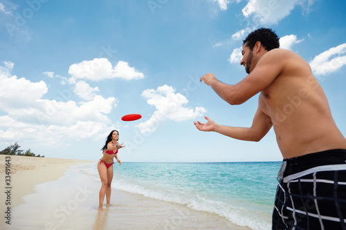 young happy man and woman playing with frisbee