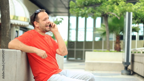 Happy man in talking on cellphone in the city
