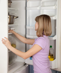 young  woman looking in  fridge