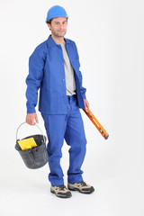 Builder holding bucket and spirit level.